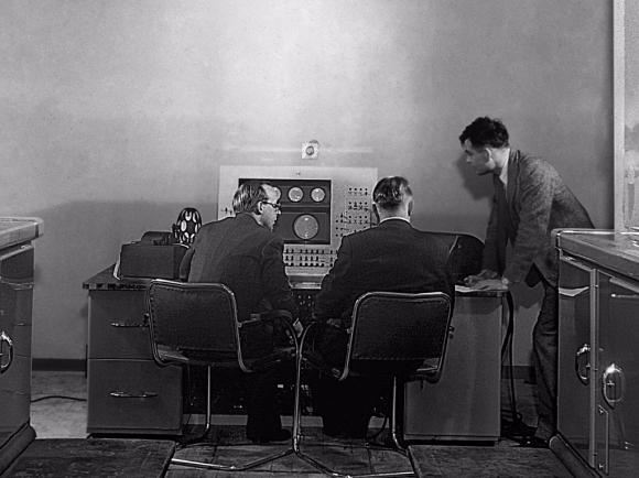 A droite, Alan Turing devant la console du Mark 2
